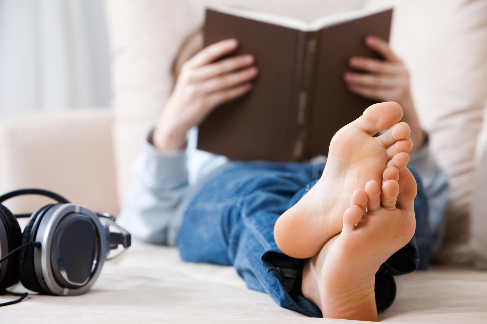 Person auf einem Bett und liest ein Buch